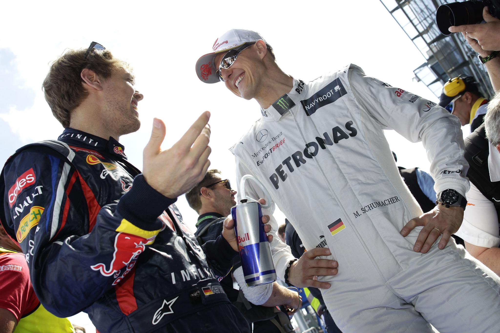 улыбающиеся Себастьян Феттель и Михаэль Шумахер на Гран-при Австралии 2012