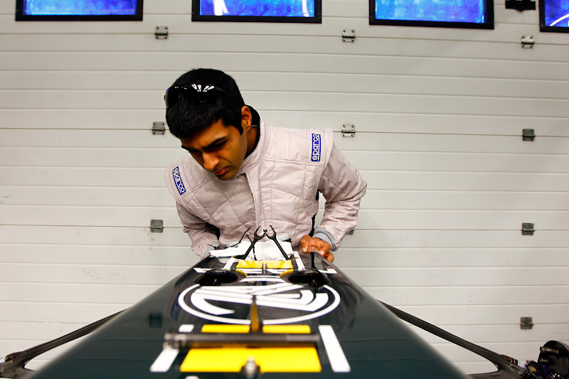 Карун Чандхок инспектирует переднее крыло Lotus T128 на предсезонных тестах 2011 в Хересе