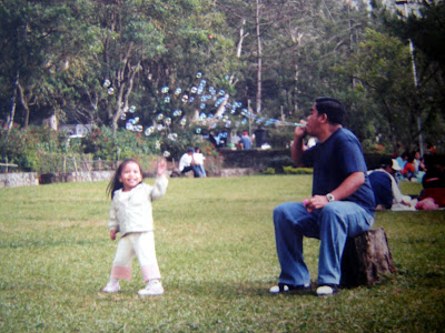 father and child playing bubbles