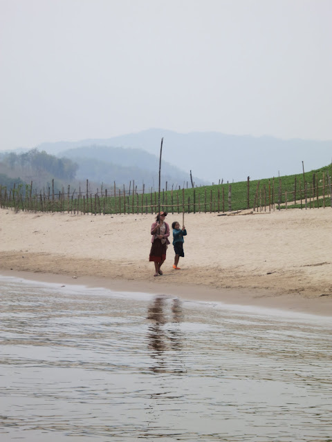 Girls collecting grasshoppers (food in these parts!) in bamboo poles.