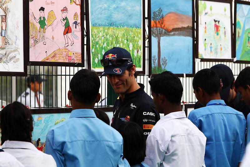 Марк Уэббер ставит автограф на рисунках индийских школьников на Гран-при Индии 2011