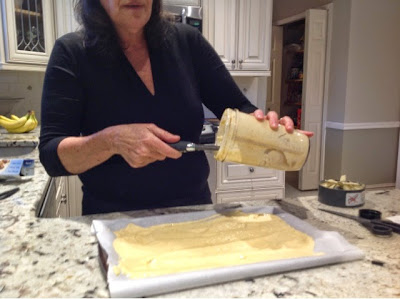 woman spreading plantain batter on parchment paper on a cookie sheet
