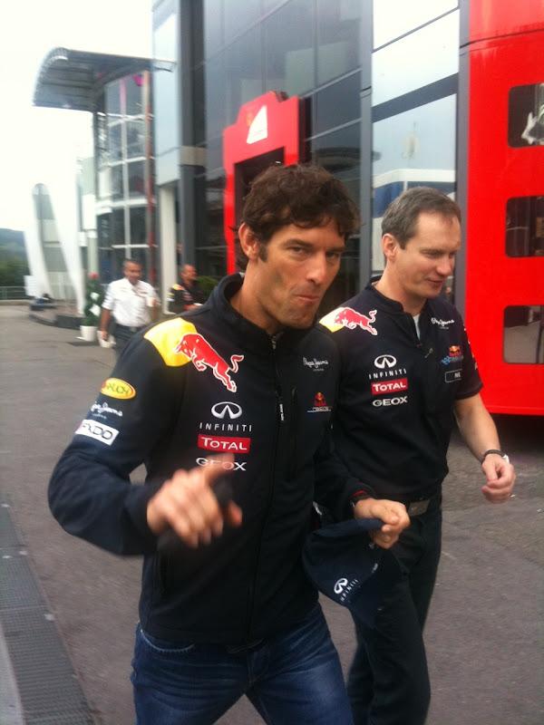 Марк Уэббер приветствует болельщиков пальцем в паддоке Спа на Гран-при Бельгии 2011 в пятницу