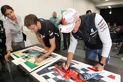 Дженсон Баттон и Михаэль Шумахер подписывают благотворительные постеры на Гран-при Японии 2011