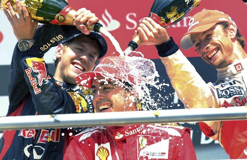 Фернандо Алонсо под душем шампанского от Себастьяна Феттеля и Дженсона Баттона на подиуме Гран-при Германии 2012