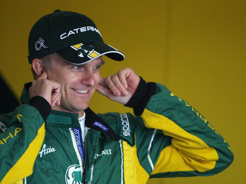 улыбающийся Хейкки Ковалайнен затыкает уши на предсезонных тестах 2012 в Барселоне 24 февраля 2012