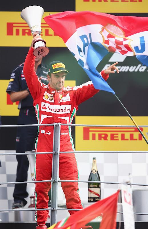 Фернандо Алонсо и большой флаг перед подиумом Монцы на Гран-при Италии 2013