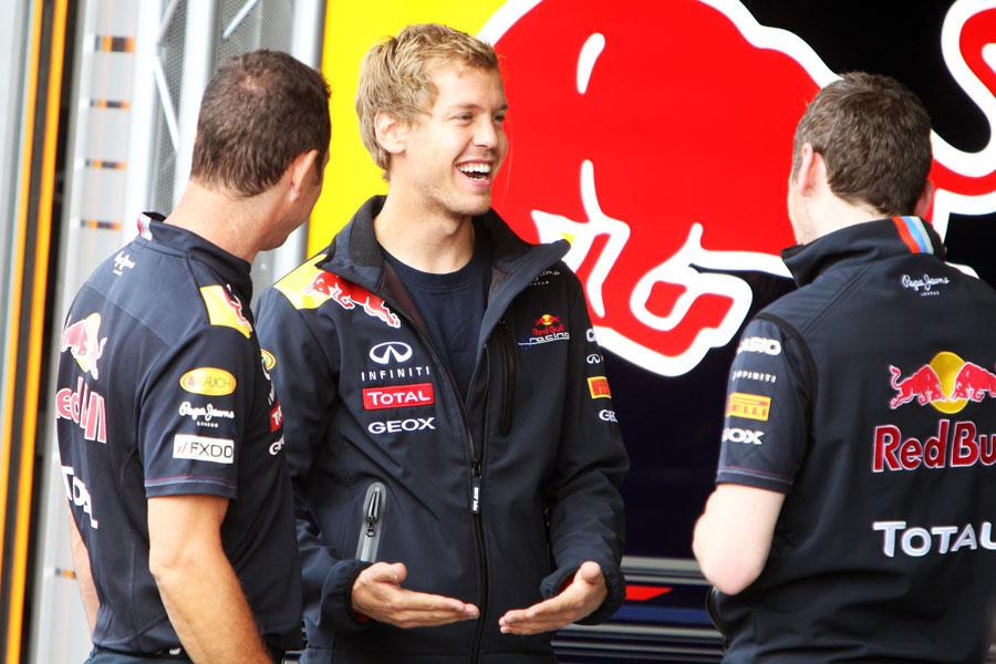 Себастьян Феттель показывает что-то веселое механикам на Гран-при Бельгии 2011
