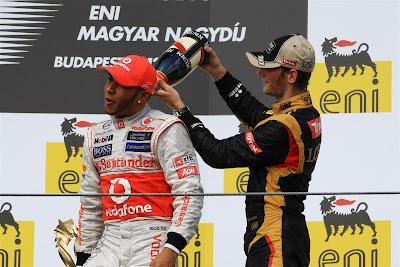 Ромэн Грожан заливает шампанское за шиворот Льюису Хэмилтону на подиуме Гран-при Венгрии 2012