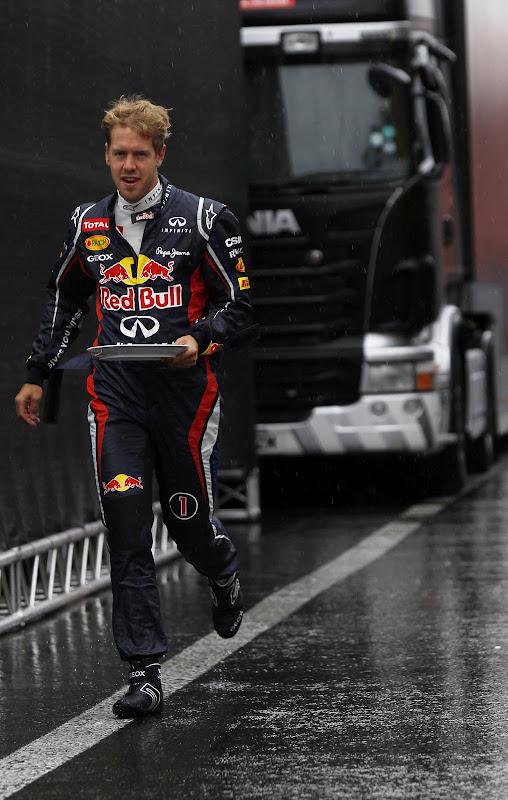 Себастьян Феттель бежит с тарелкой в паддоке под дождем Спа на Гран-при Бельгии 2012