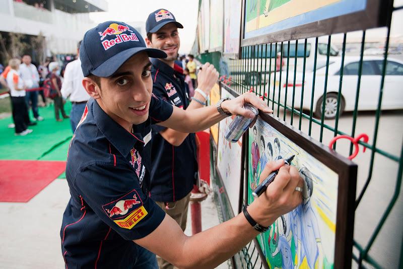 Себастьян Буэми и Хайме Альгерсуари ставят автографы на картинах на Гран-при Индии 2011