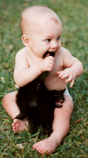 Image of a baby chewing on a cat's tail