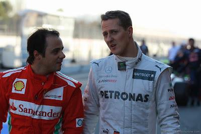 Фелипе Масса и Михаэль Шумахер разговаривают и идут по пит-лейну на предсезонных тестах 2012 в Барселоне 23 февраля 2012