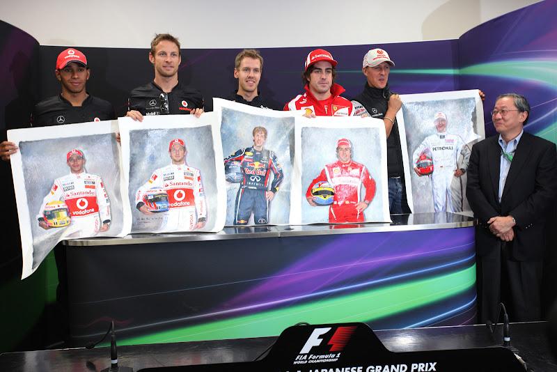 пилоты держат постеры самих себя на Гран-при Японии 2011