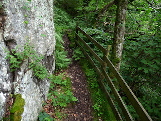 A narrow path goes around one of the many large stones.