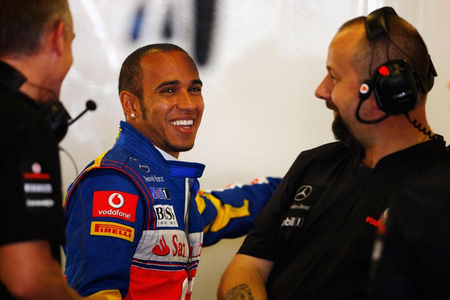 улыбающийся Льюис Хэмилтон с механиками на Гран-при Абу-Даби 2011