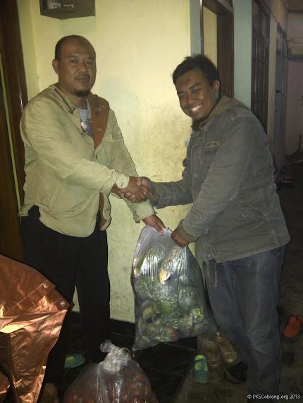 Membagikan jatah sayur untuk ditukar dengan 4 botol bekas saat kampanye di Lebak Gede