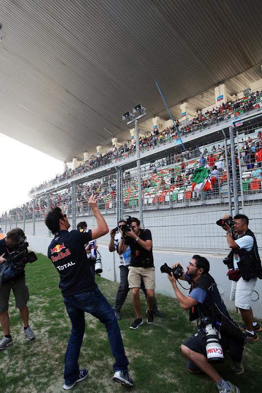 Марк Уэббер кидает индийский флаг в болельщиков на параде пилотов Гран-при Индии 2011