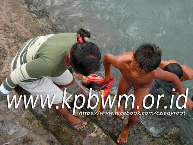 ibu dan anak saling membantu mengangkat ikan ke daratan