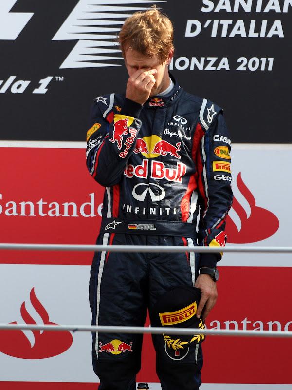 Себастьян Феттель вытирает глаза на подиуме Монцы после победы на Гран-при Италии 2011