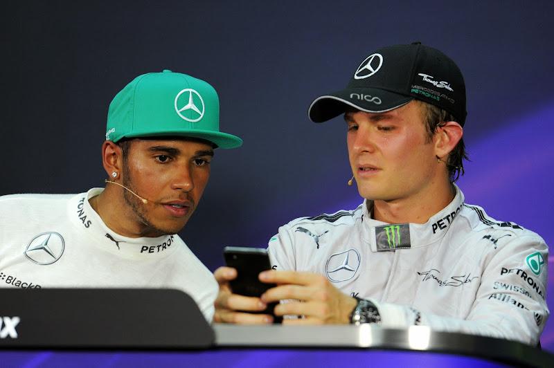 Льюис Хэмилтон и Нико Росберг разглядывают телефон на пресс-конференции после гонки на Гран-при Малайзии 2014