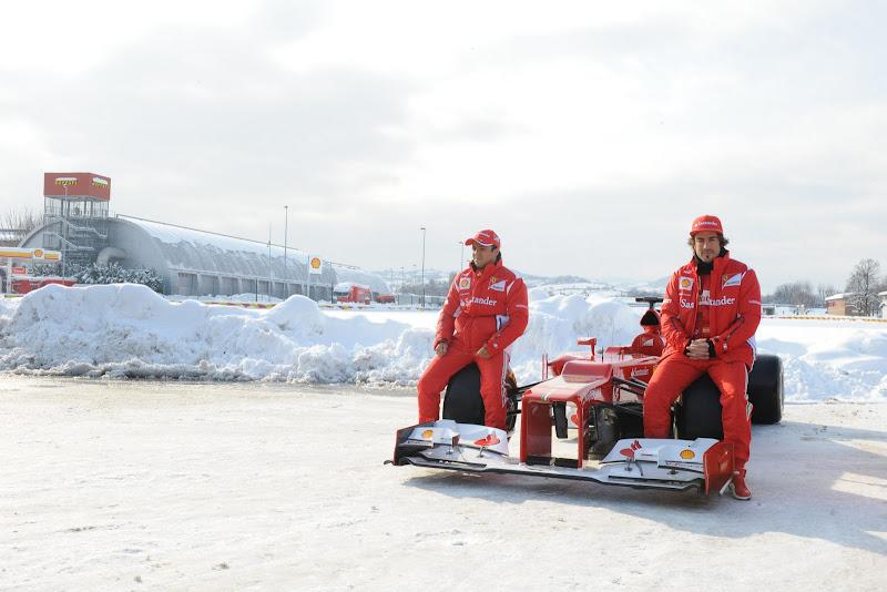 Фелипе Масса и Фернандо Алонсо сидят на передних колесах новой Ferrari F2012 на фоне заснеженной Италии 3 февраля 2012