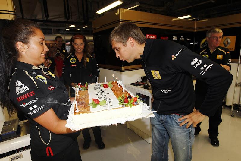 Виталий Петров в гараже Lotus Renault GP задувает свечи торта на Гран-при Италии 2011
