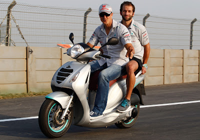 Михаэль Шумахер с механиком на мопеде на Гран-при Индии 2011