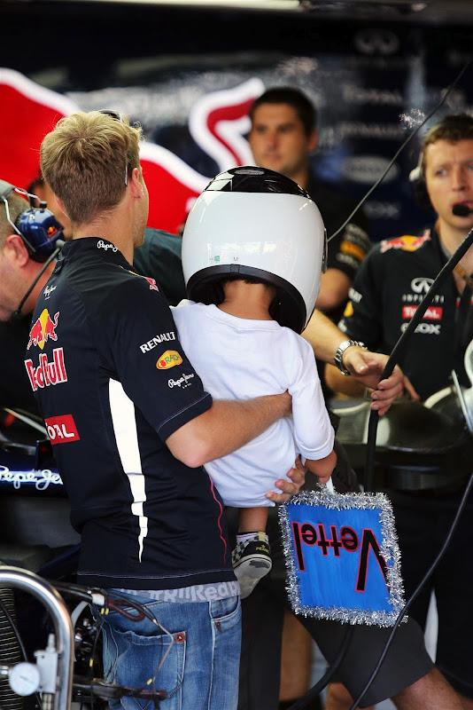 Себастьян Феттель несет на руках своего болельщика в боксы Red Bull на Гран-при Японии 2012