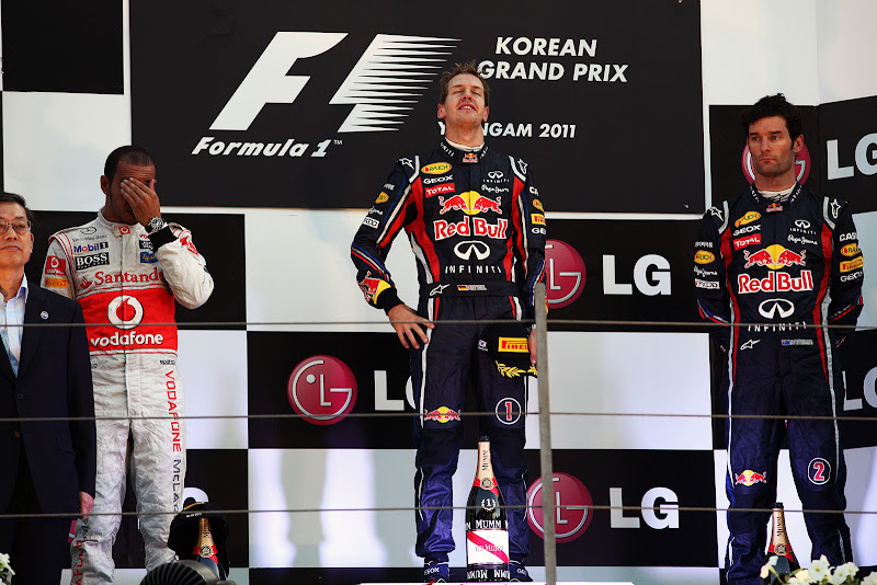фэйспалмящий Льюис Хэмилтон, Себастьян Феттель смотрящий ввысь и Марк Уэббер на подиуме Гран-при Кореи 2011