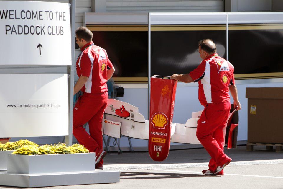 механики Ferrari с передним антикрылом направляются в паддок клуб на Гран-при Японии 2011