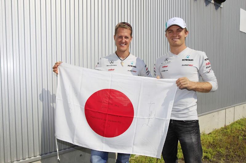 Михаэль Шумахер и Нико Росберг держат японский флаг от болельщиков Сузуки на Гран-при Японии 2011