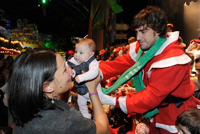 Фернандо Алонсо держит в руках ребенка на рождественском мероприятии Ferrari 18 декабря 2011