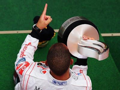 Льюис Хэмилтон с пальцем на подиуме Нюрбургринга после победы на Гран-при Германии 2011
