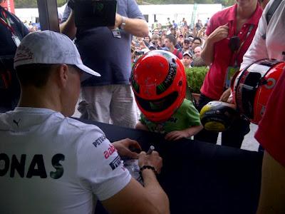 Михаэль Шумахер и ребенок в шлеме на автограф-сессии на Гран-при Австралии 2012
