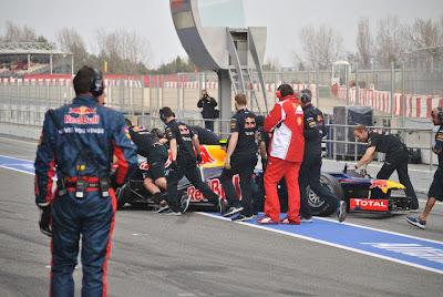 механик Ferrari шпионит за болидом Red Bull на предсезонных тестах 2012 в Барселоне