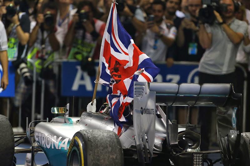 Льюис Хэмилтон с британским флагом на круге возвращения в боксы на Гран-при Абу-Даби 2014