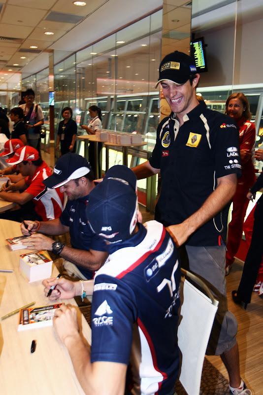 Бруно Сенна подходит к столику Пастора Мальдонадо и Рубенса Баррикелло на автограф-сессии Гран-при Сингапура 2011
