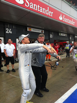 Нико Росберг и Росс Браун пускают волну по стадиону Сильверстоуна на Гран-при Великобритании 2012