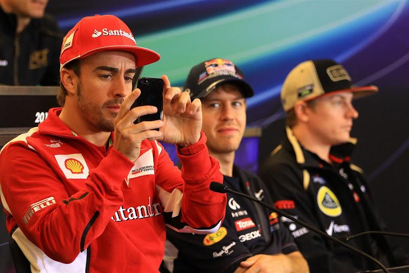Фернандо Алонсо фотографирует что-то на телефон на пресс-конференции в четверг на Гран-при США 2012