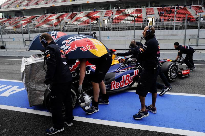 механики Red Bull закатывают болид Себастьяна Феттеля после заездов на трассе Каталунья на предсезонных тестах 2012 в Барселоне 4 марта 2012