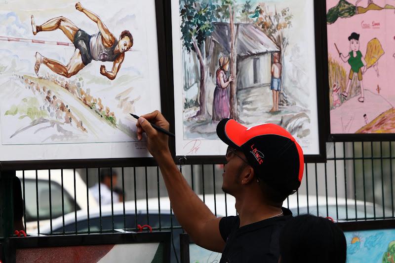 Льюис Хэмилтон ставит автограф на рисунках индийских школьников на Гран-при Индии 2011