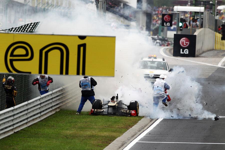 маршалы тушат горящий Lotus Renault Ника Хайдфельда на обочине Хунгароринга на Гран-при Венгрии 2011