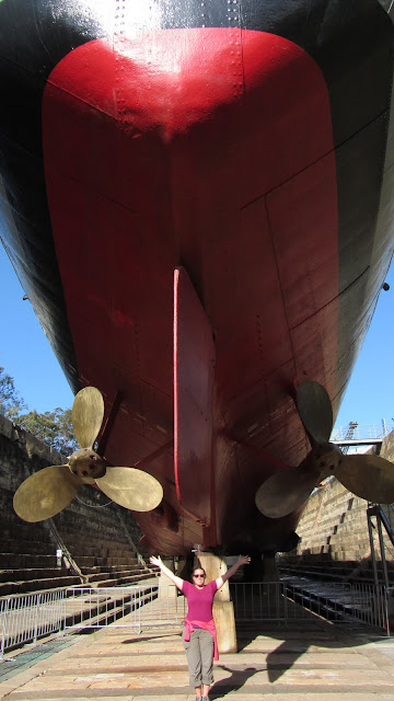 Heather standing under the HMAS Diamantina in the South Brisbane Dry Dock.
