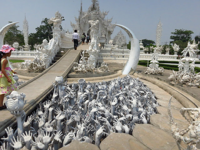 The entrance to the White Temple requires walking past these hands rising from the pits of hell.
