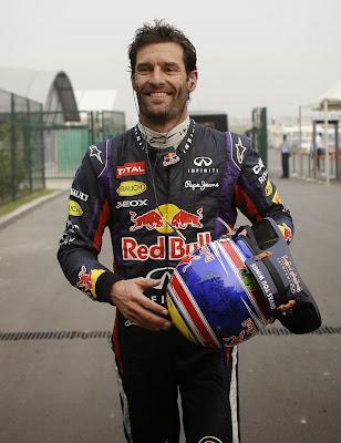 улыбающийся Марк Уэббер возвращается в боксы после схода с дистанции из-за механических проблем на своем Red Bull на Гран-при Индии 2013