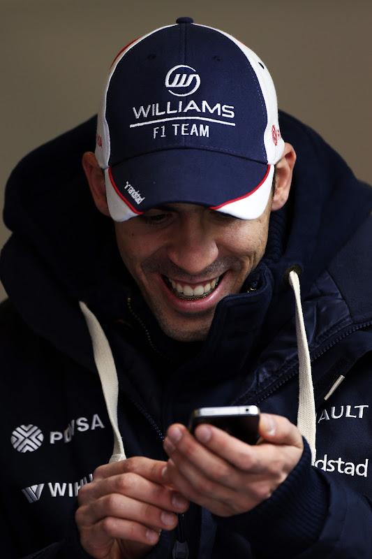улыбающийся Пастор Мальдонадо с телефоном на предсезонных тестах в Барселоне 28 февраля 2013