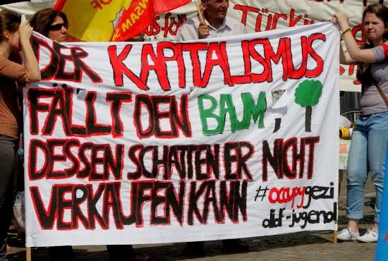 Demonstantinnen mit Transparent: »Der Kapitalismus fällt den Baum, dessen Schatten er nicht verkaufen kann«.