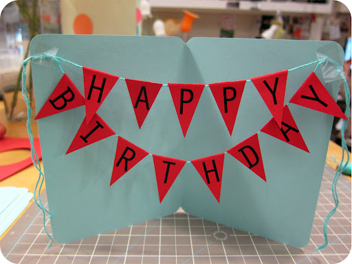 Temporarily tape your banner in an open card to determine the placement. Mark the corners where the banner will attach. Remove, and tie knots on both ends to join the two banners in the appropriate spot.