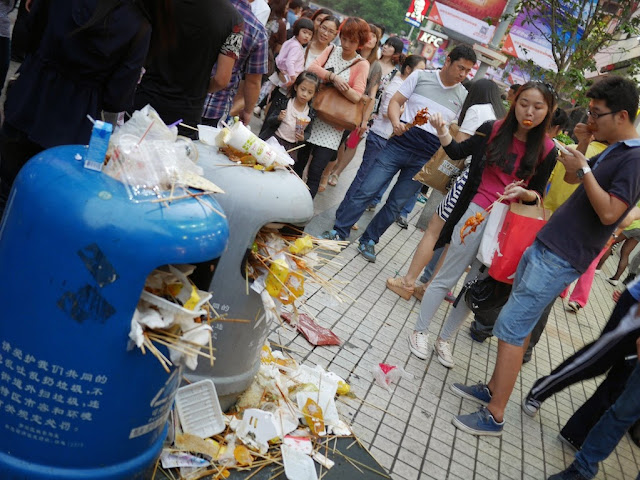young man and woman eating kebabs next to filled trashcans at Dongmen